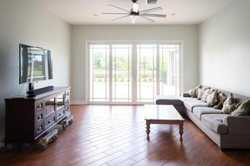 Custom Living Room renovation with large windows to let in natural light and wood floor.